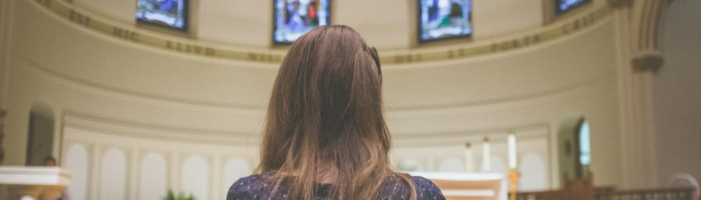 Woman stands before altar at church