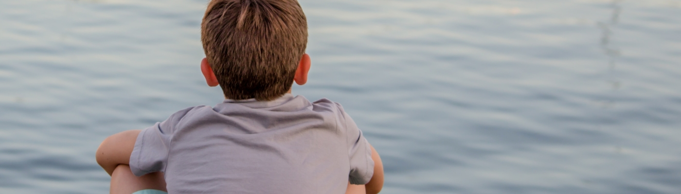 Boy in a gray T-shirt sitting on edge of still water