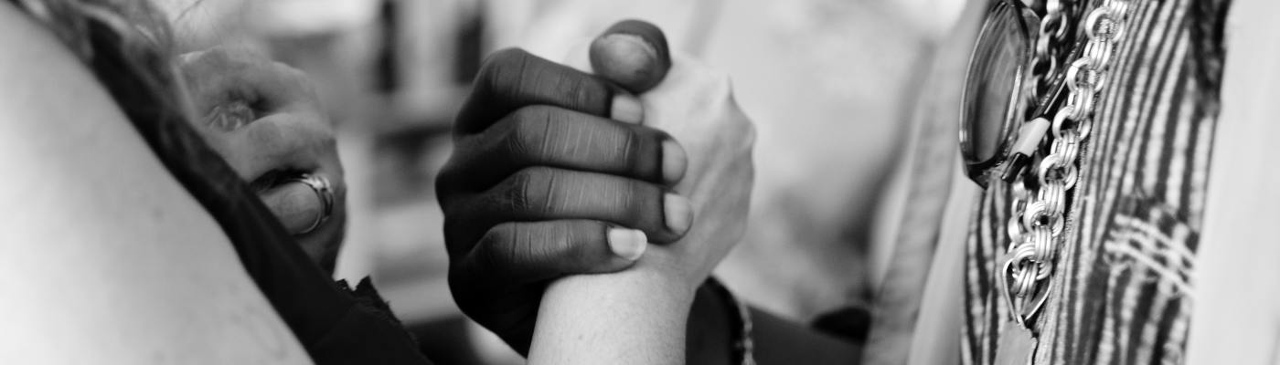 Black man and white woman joining hands in unity