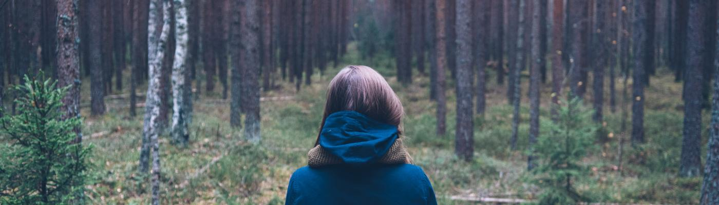 Woman standing in a European forest, with her back turned to the camera.