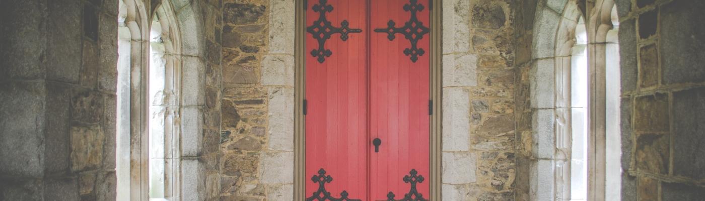 Ornate red church door, closed