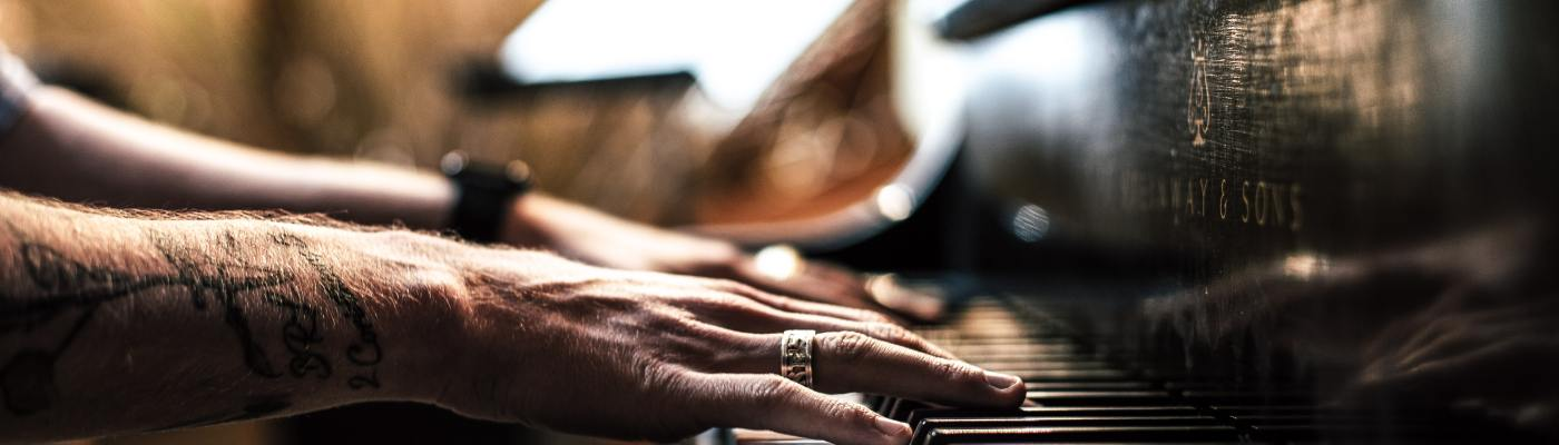 A man's hands playing a black Steinway piano
