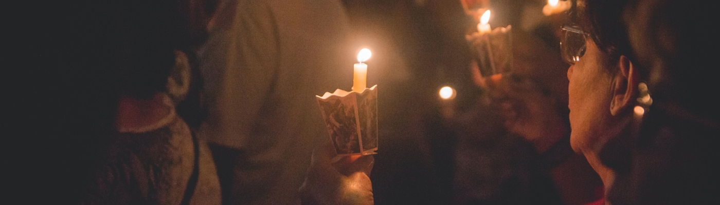 People in a church holding candles in the darkness