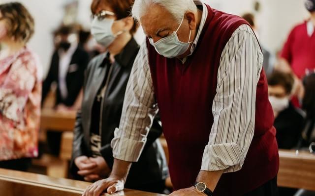 Man with surgical mask praying at church
