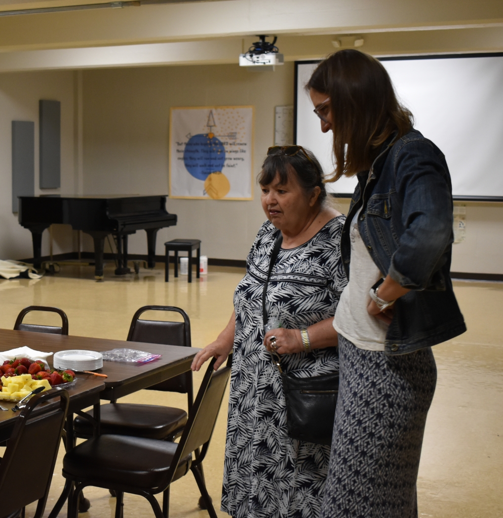 Two women talk by a table in a community room. There is pineapple and strawberries on the table.