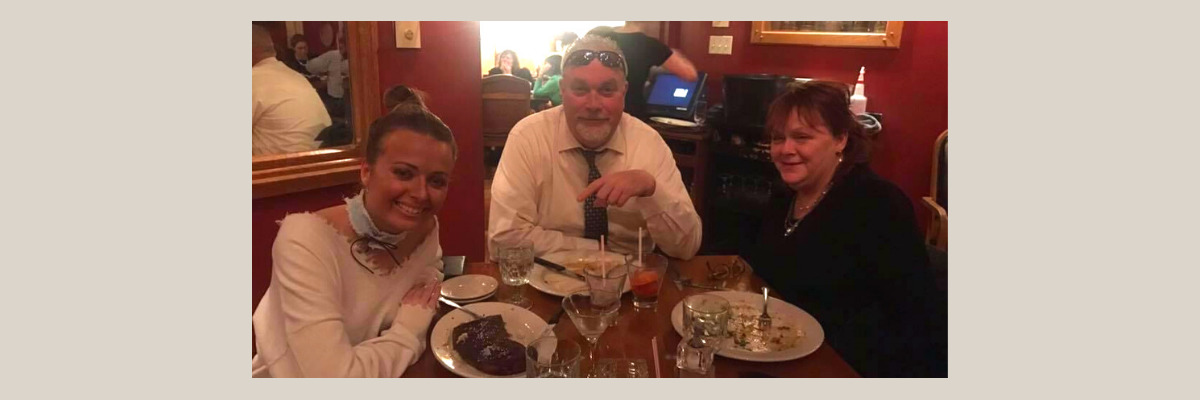 A daughter and her father and mother sit at a restaurant table together after a meal.
