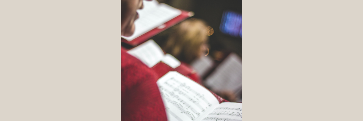 Woman in a red sweater sings choral music in a choir