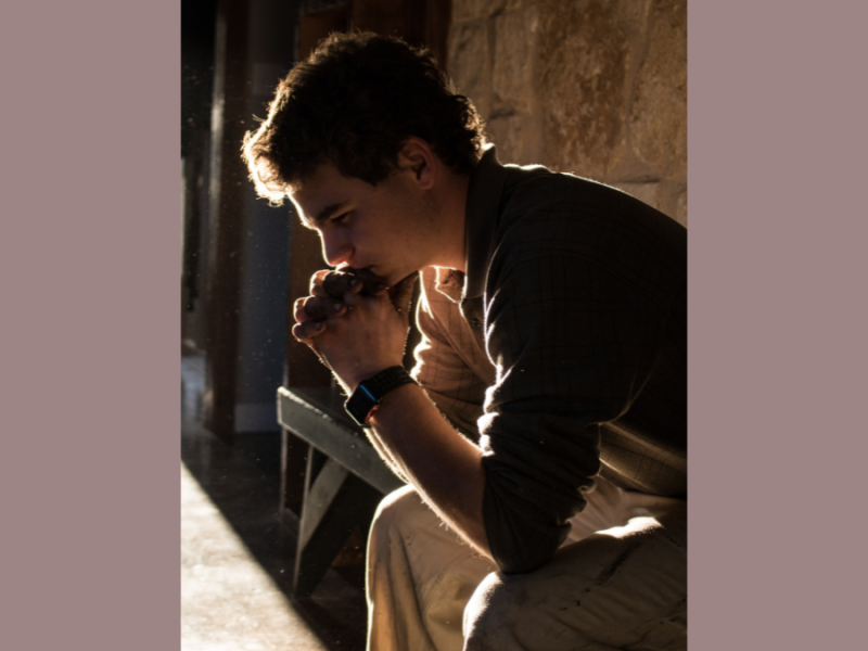 Young man with curly dark hair praying with hands folded in a stone building